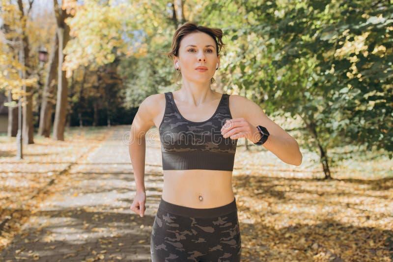 Kvinnalöpare för kvinnlig idrottsman nen som bär trådlösa hörlurar som lyssnar till musik på den smarta telefonen arkivbild