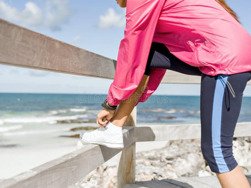 Kvinnalöpare som binder skosnöret på sjösidan arkivfoton