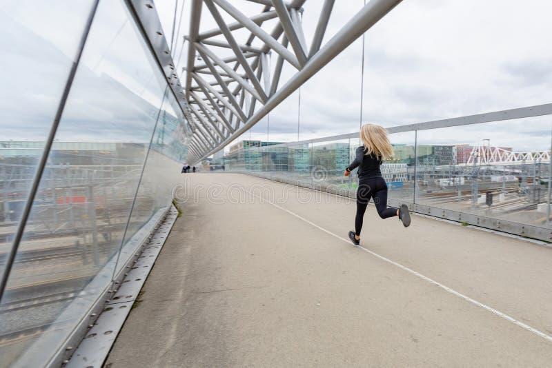 Kvinnalöpare under snabb rinnande övning i modern stad på den molniga dagen arkivbilder