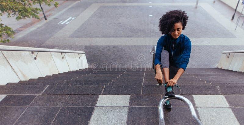 Kvinnalöparen som binder hennes sko, snör åt royaltyfri fotografi
