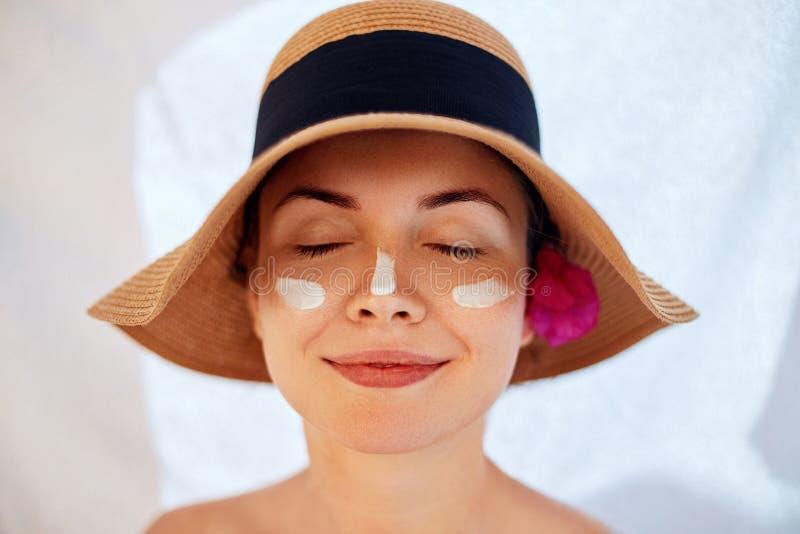 Kvinnaleende som applicerar solkräm på framsida Skincare Kroppsolskydd sunscreen arkivbilder