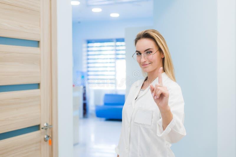Kvinnaleendet för den medicinska doktorn, dräkten för kirurgi för sjuksköterskakläder den vita, punktfinger upp, begreppet av ann fotografering för bildbyråer