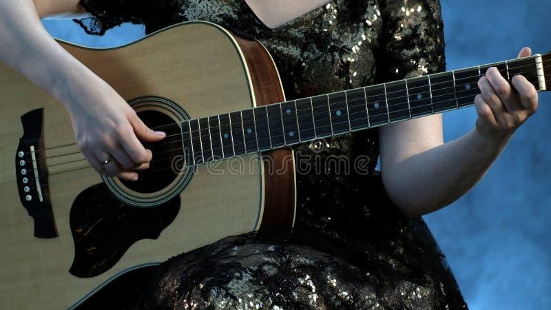 Kvinnalek på gitarren Fingrarna av vänstersidahanden av den härliga flickaklämman på raderna ett ackord i e-minderårig royaltyfri foto