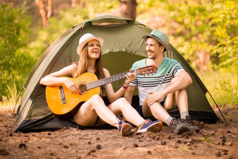 Kvinnalekgitarr ?ventyra, resa, turism och folkbegreppet - att le par med gitarren, i att campa royaltyfri fotografi