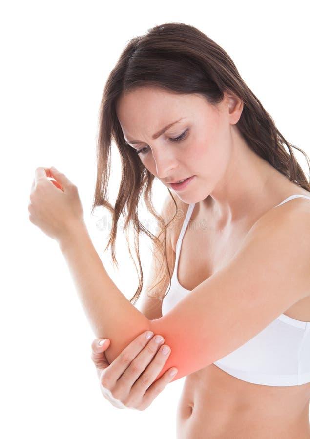 Kvinnalidande från armbåge smärtar royaltyfria foton