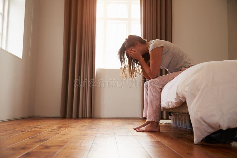 Kvinnalidande från fördjupningssammanträde på säng i pyjamas royaltyfri fotografi