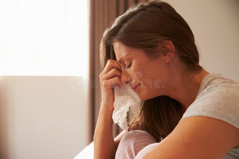 Kvinnalidande från fördjupningssammanträde på säng och gråt fotografering för bildbyråer