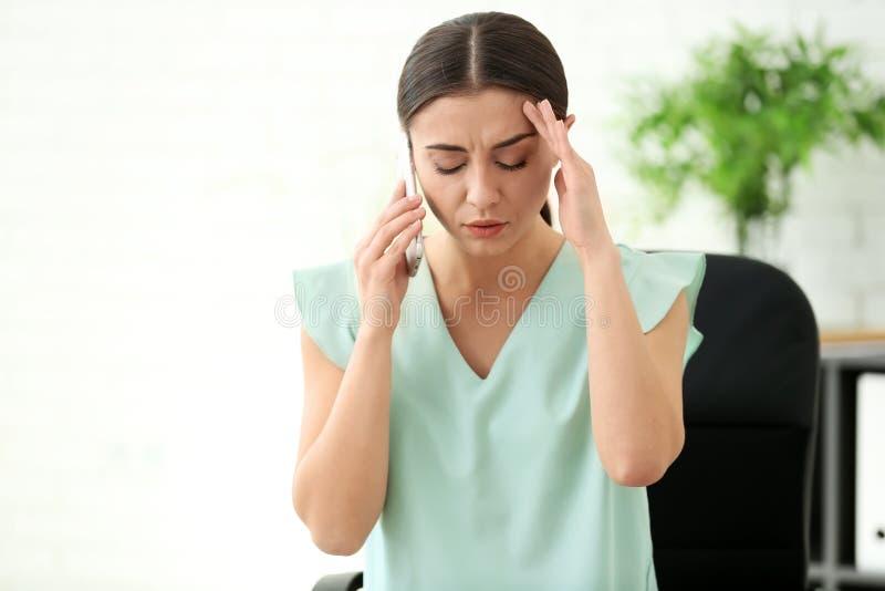 Kvinnalidande från huvudvärk, medan tala vid mobiltelefonen i regeringsställning arkivfoto