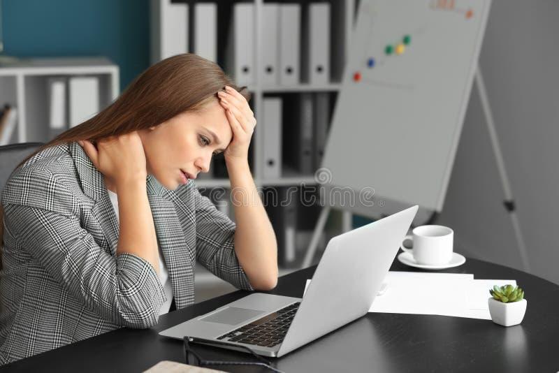 Kvinnalidande från huvudvärk och halsen smärtar i regeringsställning arkivbilder