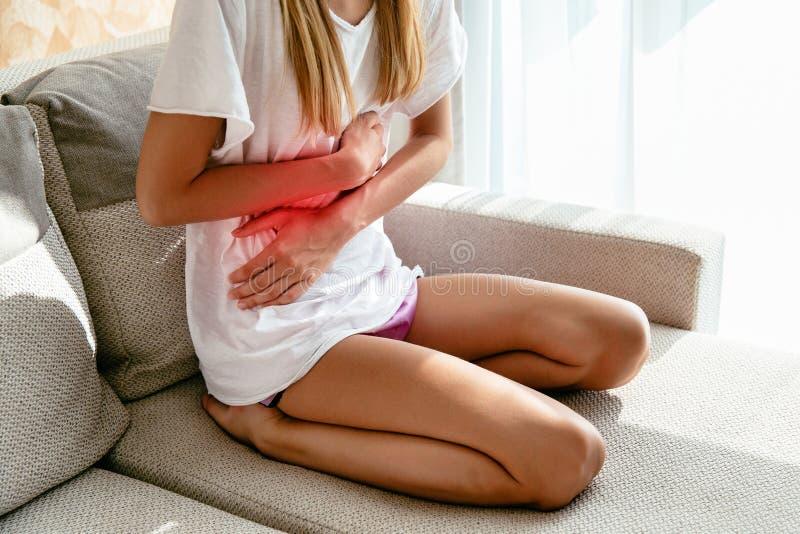 Kvinnalidande från magen smärtar, sammanträde på soffan hemma royaltyfri bild