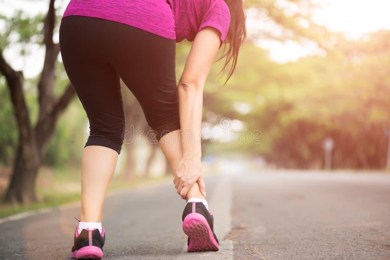 Kvinnalidande fr?n en ankelskada, medan ?va Rinnande sportskadabegrepp royaltyfri bild