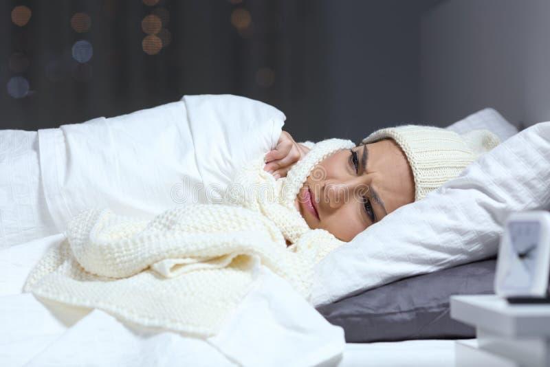 Kvinnalidandeförkylning i en säng i vinter arkivfoto