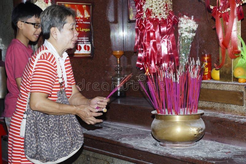 Kvinnaljusstearinljuset och dyfter klibbar för att be för bortgångna släktingar i kinesisk tempel i Manila arkivbilder