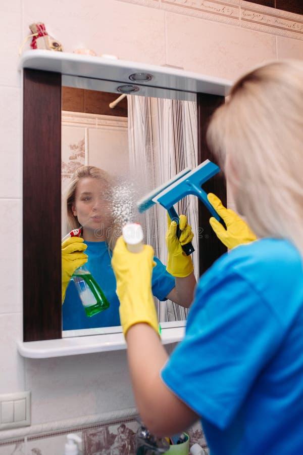 Kvinnalokalvård med sprej och användaskrapan för att tvätta spegeln på badrummet arkivbilder