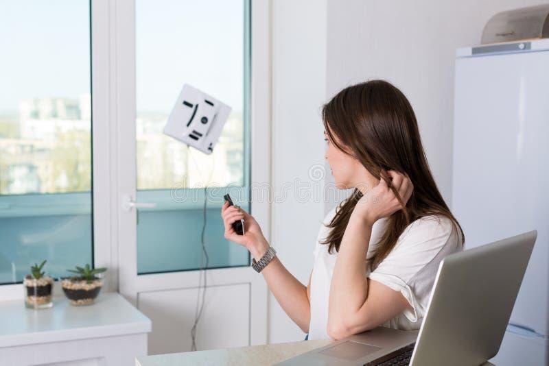 Kvinnalokalvårdfönster med det robotic rengöringsmedlet royaltyfria bilder