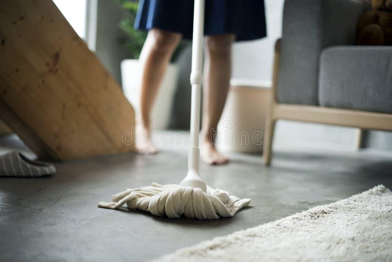Kvinnalokalvårdhem med golvmopp arkivfoton