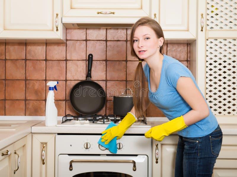 Kvinnalokalvårdhus Polerande ugn för härlig flicka i kitchen royaltyfri bild
