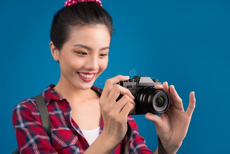 Kvinnalopp Ung härlig asiatisk kvinnahandelsresande som tar bilder på blå bakgrund fotografering för bildbyråer