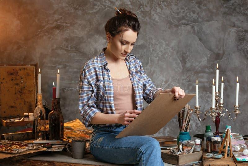 Kvinnamålaresammanträde på tabellen, teckningen och le idérikt begrepp Dra tillförsel, borstar olje- målarfärger, konstnär fotografering för bildbyråer