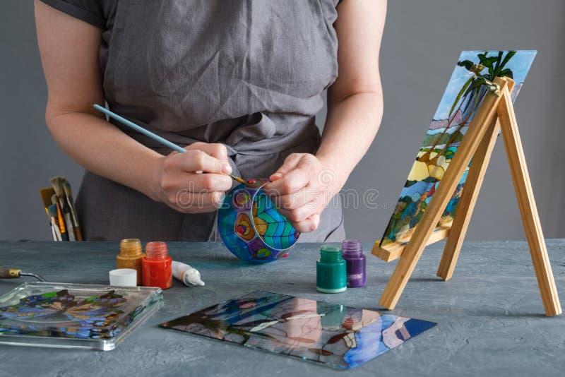 Kvinnamålning med målat glassmålarfärger på en exponeringsglasvas royaltyfria bilder