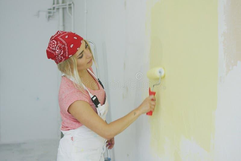 Kvinnamålningvägg med rullen royaltyfri bild