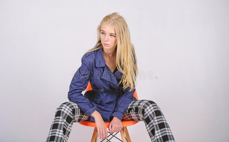 Kvinnamakeupframsida som poserar laget p? modern stol Trendigt lag Kl?der och tillbeh?r Blandande stilar Flickamode arkivfoton