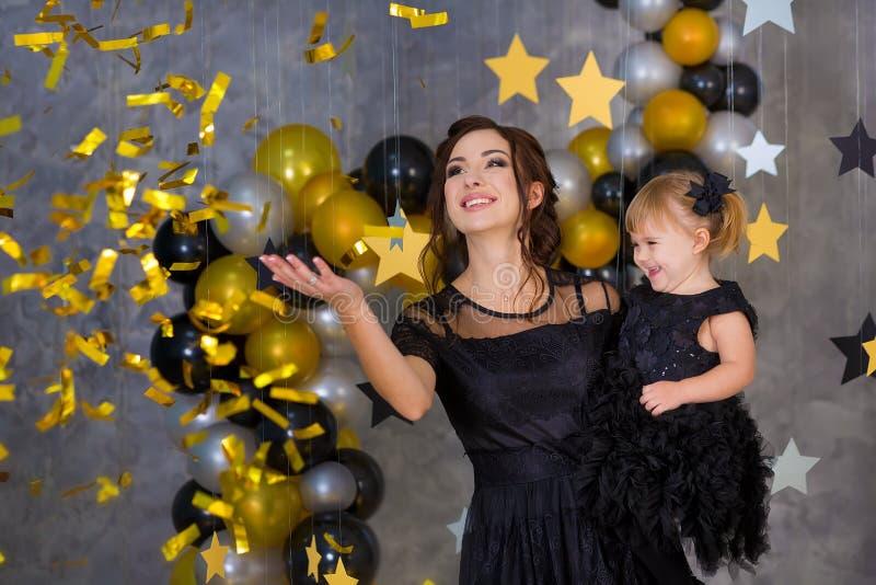 Kvinnamaktpartiet med den härliga modellmodern och gulligt behandla som ett barn iklädda luftiga svarta maskeradkläder för dotter arkivbild