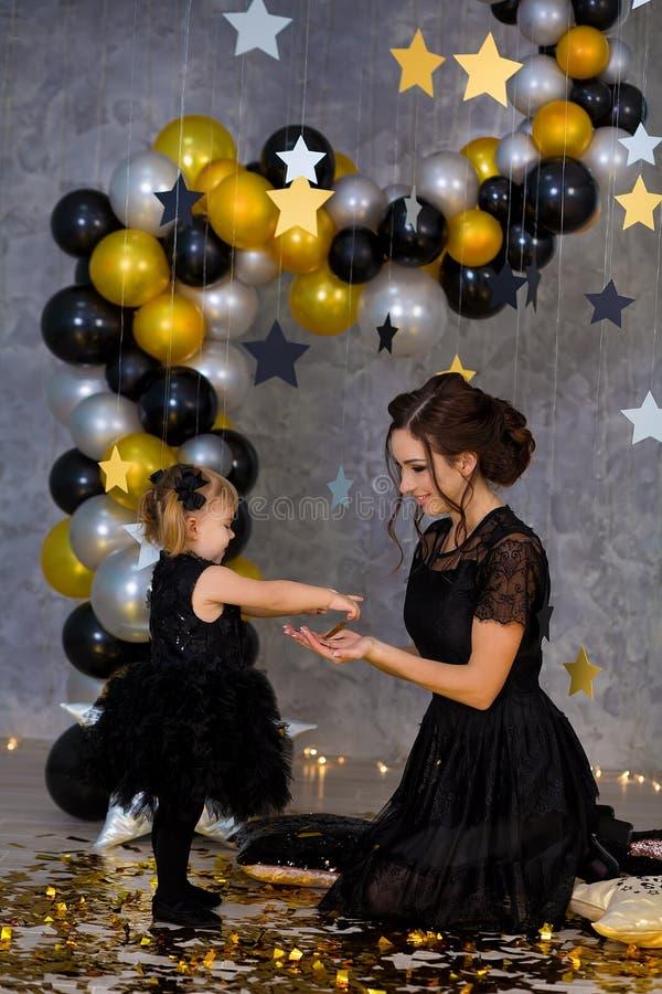 Kvinnamaktpartiet med den härliga modellmodern och gulligt behandla som ett barn iklädda luftiga svarta maskeradkläder för dotter arkivfoton