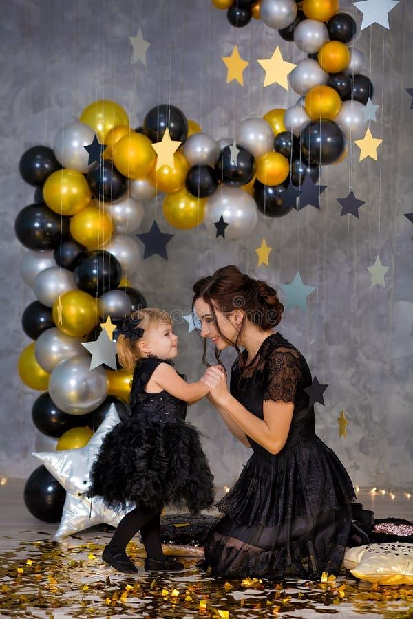Kvinnamaktpartiet med den härliga modellmodern och gulligt behandla som ett barn iklädda luftiga svarta maskeradkläder för dotter royaltyfria foton