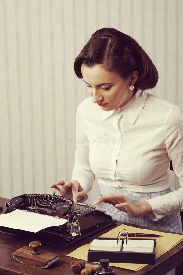 Kvinnamaskinskrivning i hennes kontor royaltyfri fotografi