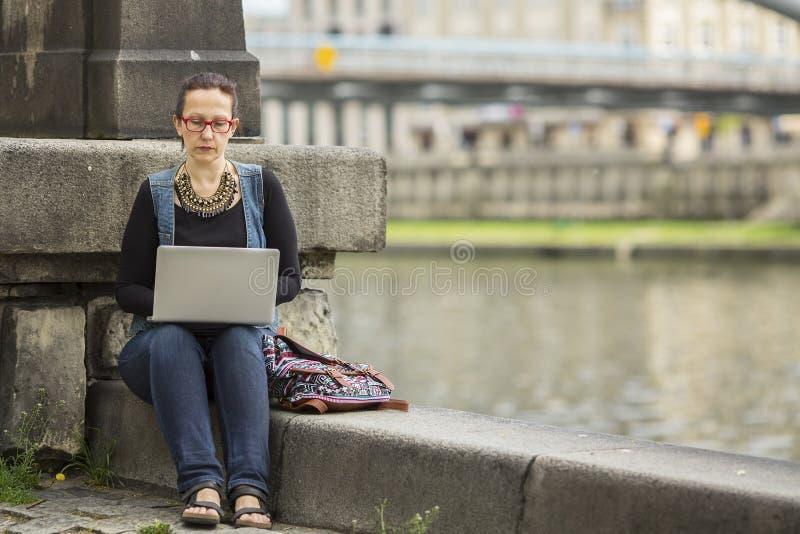 kvinnamaskinskrivning på bärbar datorsammanträde på invallning av floden i den gamla staden arkivfoton