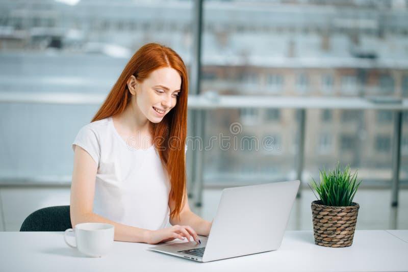 Kvinnamaskinskrivning på bärbara datorn på arbetsplatskvinnan som arbetar i inrikesdepartementethandtangentbord royaltyfria bilder