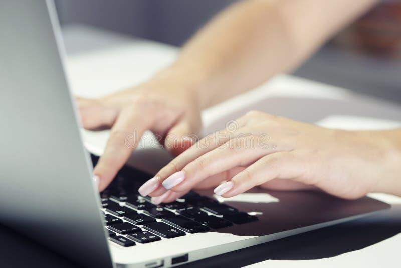 Kvinnamaskinskrivning på bärbara datorn på arbetsplatskvinnan som arbetar i inrikesdepartementethandtangentbord royaltyfri fotografi