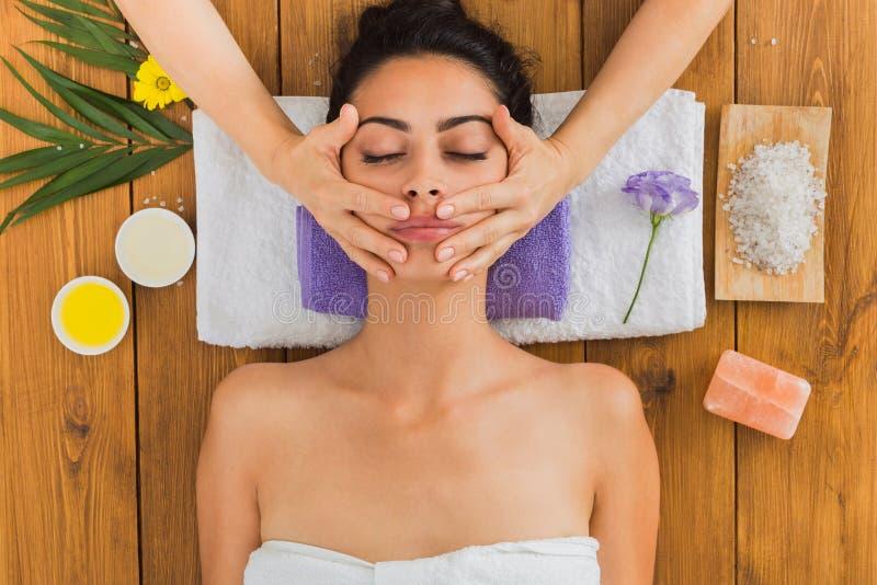 Kvinnamassagisten gör massage för lyfta för framsida i brunnsortwellnessmitt arkivbild