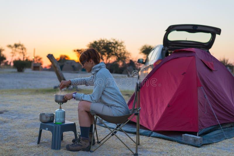 Kvinnamatlagning med gasugnen i campa plats på skymning Gasgasbrännare, kruka och rök från kokande vatten, tält i bakgrunden _ arkivfoto