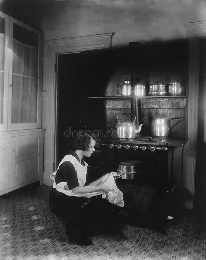 Kvinnamatlagning med ugnen royaltyfri foto