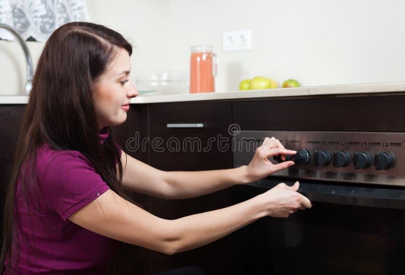 Kvinnamatlagning något i ugnen arkivfoton