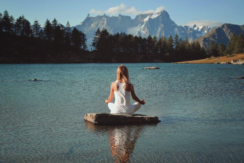 Kvinnameditation i bergsjön royaltyfri fotografi