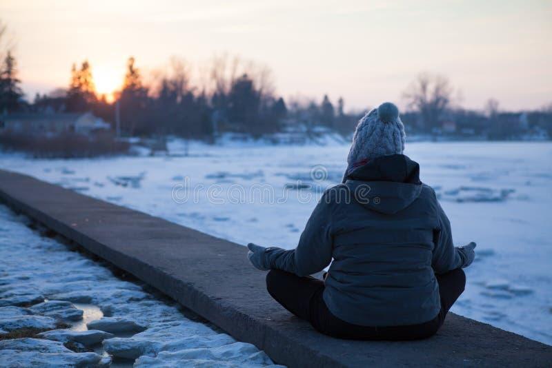 Kvinnameditation i vinterdag på floden arkivbilder
