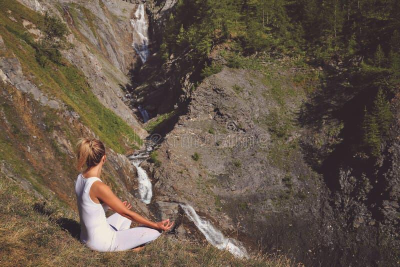 Kvinnameditation nästan en vattenfall arkivfoto