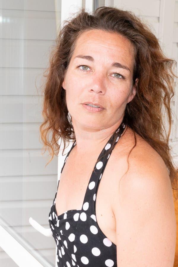 Kvinnamitt åldrades den lockiga brunettcloseupståenden i träväggbakgrund royaltyfria bilder