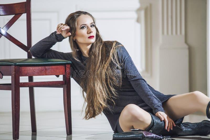 Kvinnamodell i klänning med innegrejkängor och ljusa röda kanter fotografering för bildbyråer