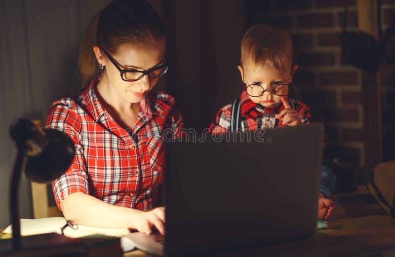Kvinnamoder som arbetar med en behandla som ett barn som är hemmastadd bak en dator arkivfoto