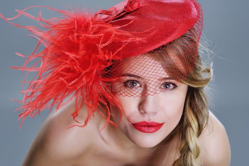 Kvinnamodestående i röd tappninghatt med fjädrar royaltyfria bilder