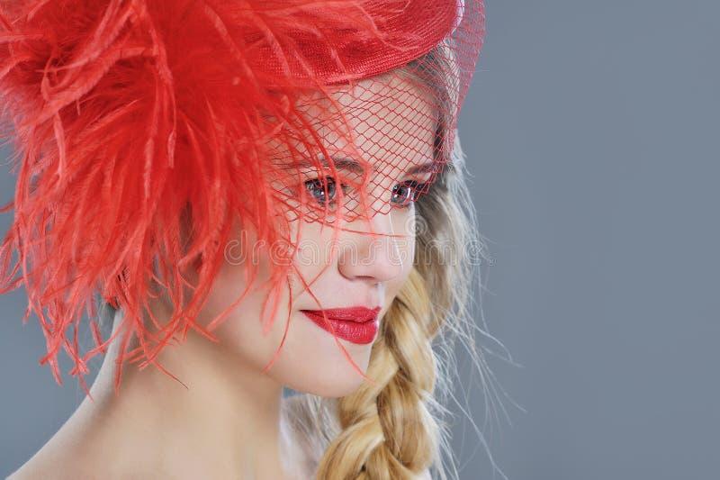 Kvinnamodestående i röd tappninghatt med fjädrar fotografering för bildbyråer