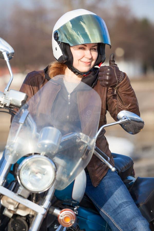 Kvinnamotorcyklist i brunt läderomslag och den vita störthjälmvisningtummen upp tecken med handen royaltyfri bild