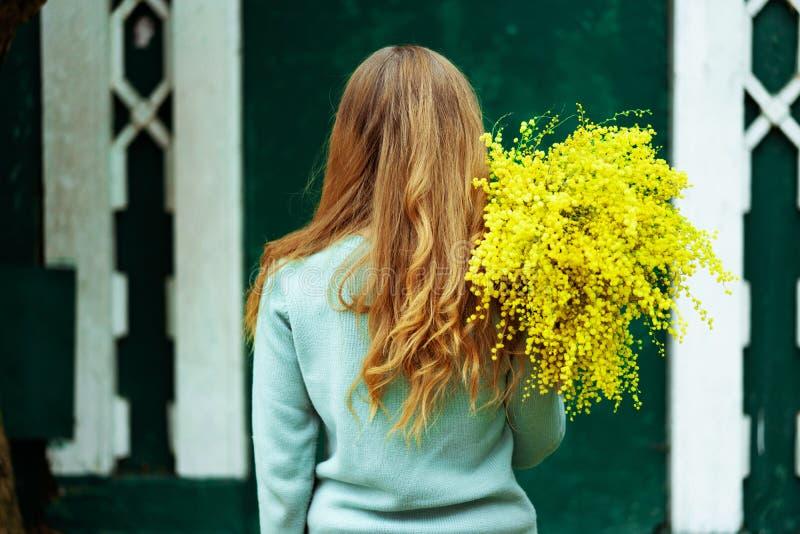 Kvinnanärbildbaksida med buketten av det gula lynnet och helgen för mimosavårferie arkivfoton
