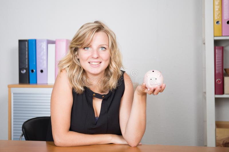 Kvinnan är det finansiella budget- besparingbegreppet för den hållande spargrisen på kontorsskrivbordet arkivfoton