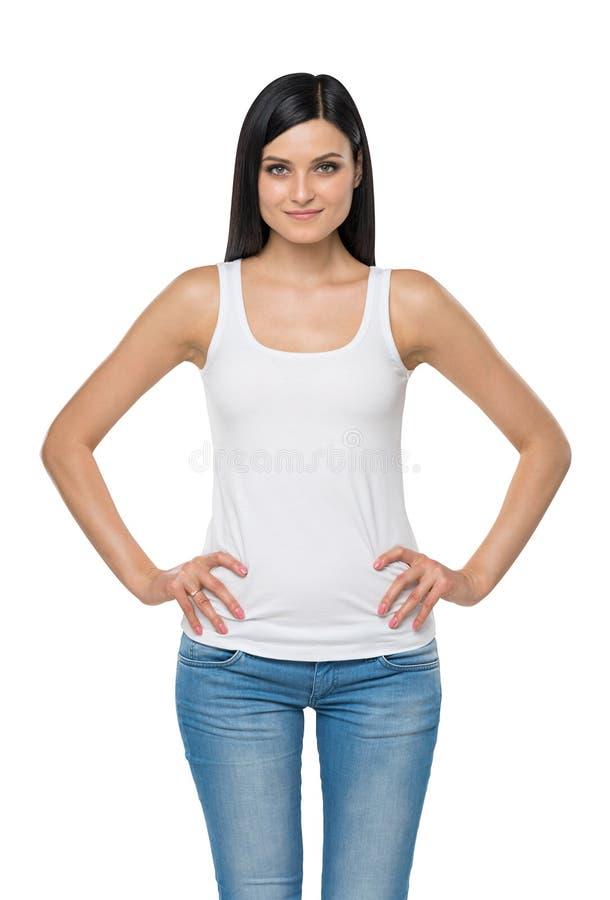 Kvinnan är i en vit ärmlös tröja och blå jeans isolerat royaltyfri bild