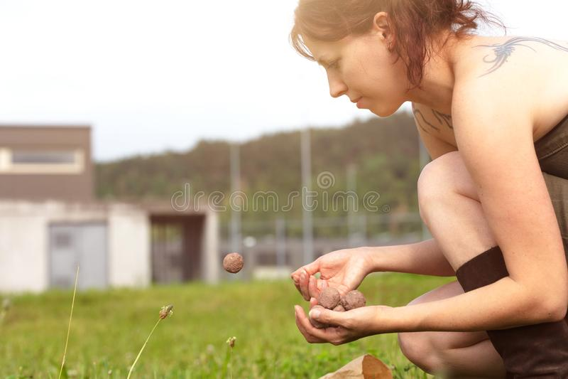 Kvinnan är rymma, och kasta kärna ur bollar eller kärna ur bombarderar framme av en ful grå byggnad royaltyfri bild